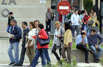 Mujeres y hombres se dirigen a su puesto de trabajo en la sede central de la Administracion vasca, en Vitoria.