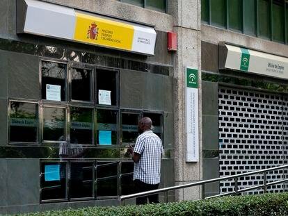 Un hombre lee la información en la puerta de la oficina de empleo de Huerta de la Salud (Sevilla).