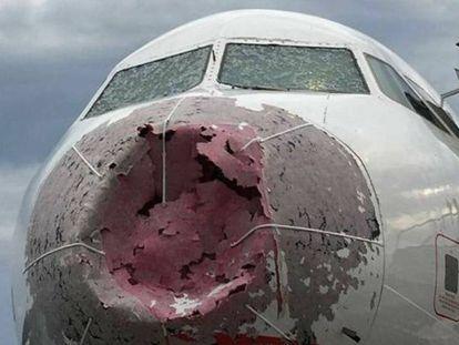 La cabina de un avión, destrozada por el granizo.