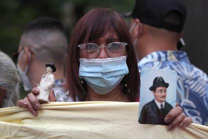 Una mujer sostiene una figura y una fotografía del médico venezolano José Gregorio Hernández.