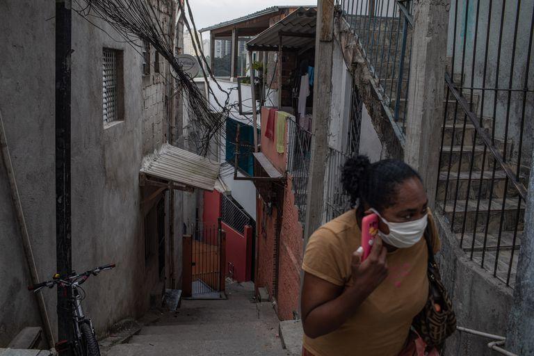 Una mujer con mascarilla utiliza su teléfono móvil en la favela de Paraisópolis, la más grande de São Paulo, el 6 de mayo de 2020.
