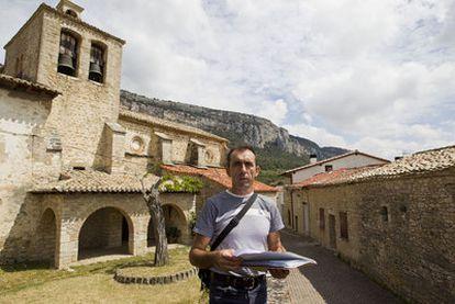 El exalcalde de Ziritza (Navarra) muestra la documentación sobre los edificios de su pueblo, con la iglesia a su espalda.