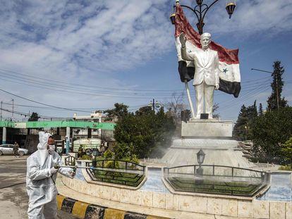 Un trabajador desinfecta una estatua del expresidente sirio Hafez el Asad, en la ciudad de Qamishli, en el nordeste de Siria, el pasado martes.