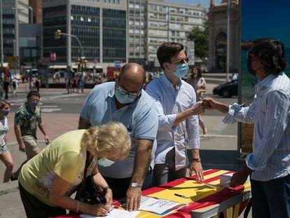 Una ciudadana firma en contra de los indultos este domingo en la plaza de Espanya de Barcelona.