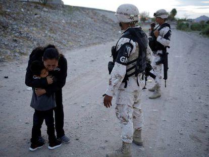 Lety Perez, inmigrante guatemalteca, abaraza a su hijo ante los guardias fronterizos de México en Ciudad Juarez.