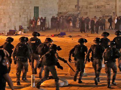 Policías israelíes dispersan a ciudadanos palestinos, en la noche del viernes, en la explanada de las mezquitas de Jerusalén.