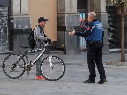 Un policía informa a un ciudadano de la prohibición de montar en bici tras la aprobación, este domingo, del real decreto que establece las medidas del estado de alarma para hacer frente a la pandemia del Covid-19.