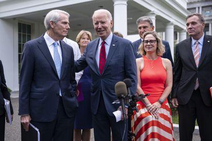 Joe Biden anuncia el acuerdo sobre el plan de infraestructuras, rodeado por los senadores que lo negociaron, este jueves en la Casa Blanca.