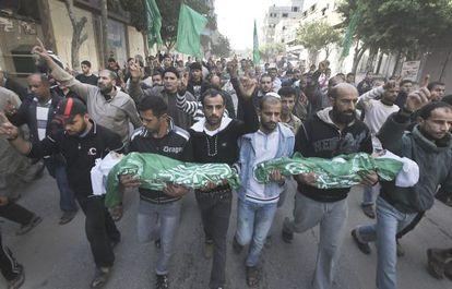 Hombres palestinos sostienen los cadáveres de dos niños, durante su funeral en Gaza.