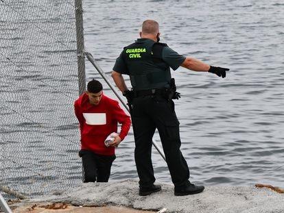 Un Guardia Civil observa a uno de los inmigrantes en uno de los espigones fronterizos de Ceuta.