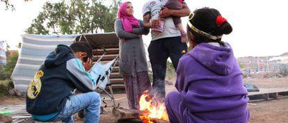 Una familia procedente de Siria se prepara para cenar a las afueras del centro de inmigrantes de Melilla.