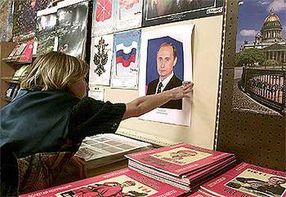 Una mujer cuelga una foto de Putin en la tienda en la que trabaja, ayer en San Petersburgo.