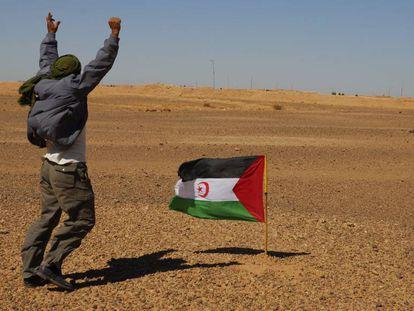 Un miembro del Frente Polisario se manifiesta ante los soldados marroquíes, al fondo de la imagen,  apostados en el muro construído por Marruecos.