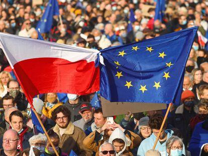 Varios manifestantes ondean banderas de Polonia y la UE, en una marcha este domingo en Cracovia.