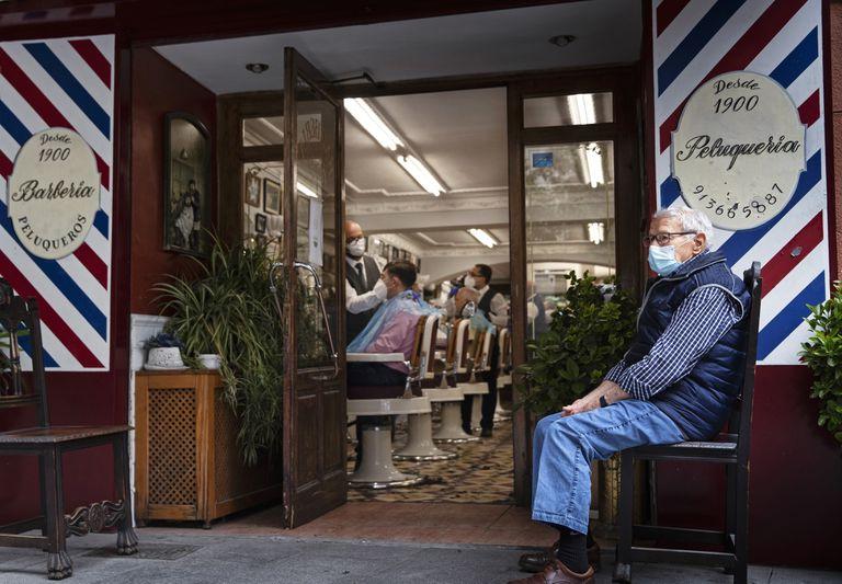 Un hombre espera su turno en el exterior de una peluquería en el centro de Madrid, este lunes.