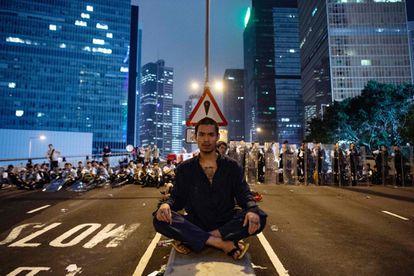 Un hombre protesta la ley de extradición en Hong Kong se sienta frente a un grupo de policías.