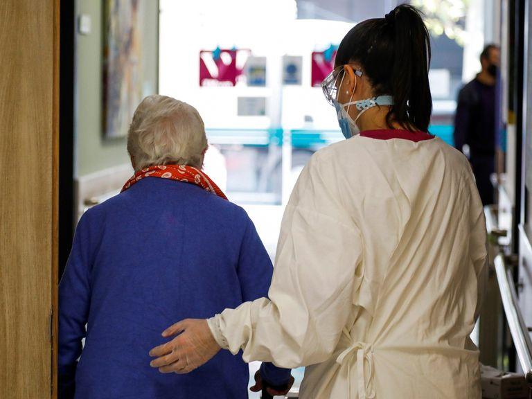 Una trabajadora de una residencia de mayores ayuda a una paciente, este lunes, en Madrid.