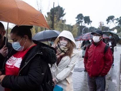 Becky Harris, en el centro con un abrigo blanco, hace cola con otros inmigrantes en la principal comisaría de policía de extranjería en Madrid, en Aluche.