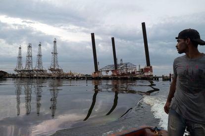 Un pescador observa una vetusta infraestructura en el lago Maracaibo (Venezuela).