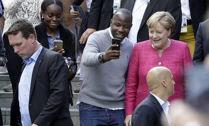 Angela Merkel posa con un visitante en el día de puertas abiertas de la cancillería en Berlín.
