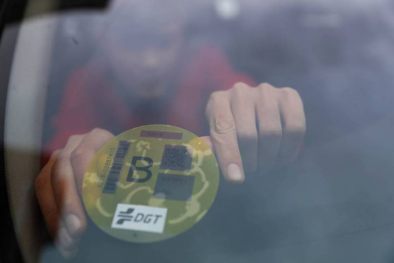 Un hombre coloca la etiqueta ambiental de la DGT en la luna de su coche.