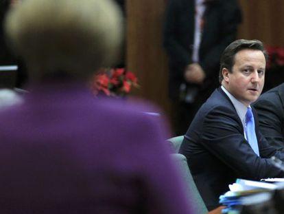 Cameron mira a Merkel (de espaldas) en la cumbre europea.