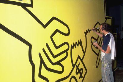 El artista Keith Haring pinta su trabajo en una gran pared amarilla para una exposición de arte en mayo de 1985.