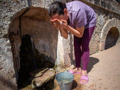 Una mujer se lava la cara con agua del grifo que hay en el exterior del manantial de El Tempul en San José del Valle (Cádiz), cuyo Ayuntamiento está enfrentado al de Jerez por su explotación