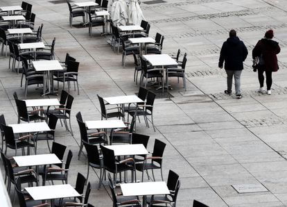 Dos personas caminan por la Plaza del Castillo de Pamplona.