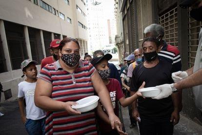 La pareja Maxwell Oliveira y Verônica Medeiros reciben la donación de alimentos en São Paulo.