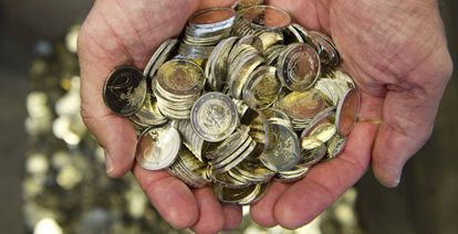 Un hombre sostiene varias monedas de euro.