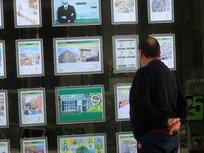 Anuncios de pisos publicitados en el escaparate de una agencia inmobiliaria.