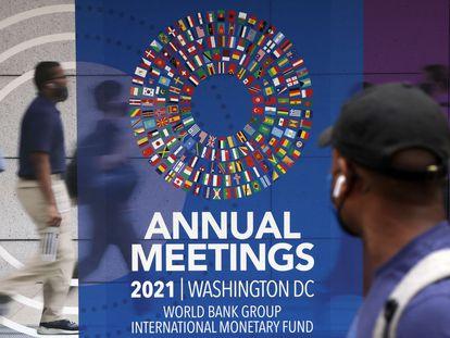 Un hombre pasa por un cartel de las reuniones anuales del Grupo del Banco Mundial y el Fondo Monetario Internacional, el 11 de octubre de 2021 en Washington.