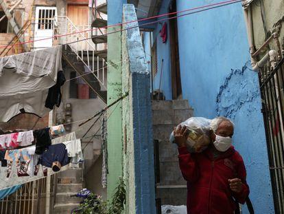 Un hombre carga una bolsa de comida repartida por una ONG en una favela de Río de Janeiro, el pasado mes de junio.