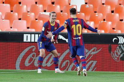 Messi y Griezmann festejan un gol al Valencia en el último duelo liguero.