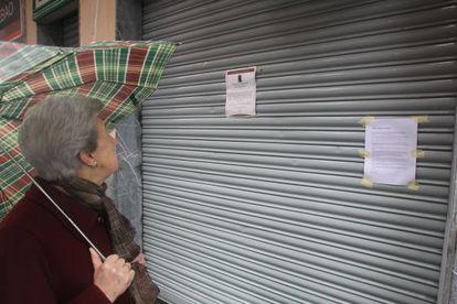 Una paseante observa la esquela de Iñigo Cabacas en la puerta del bar Biltoki, propiedad de su padre