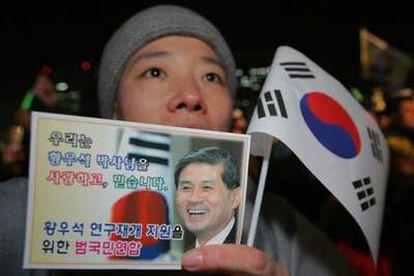 """Una monja budista muestra ayer en Seúl un mensaje que dice: """"Amamos y creemos al doctor Hwang""""."""