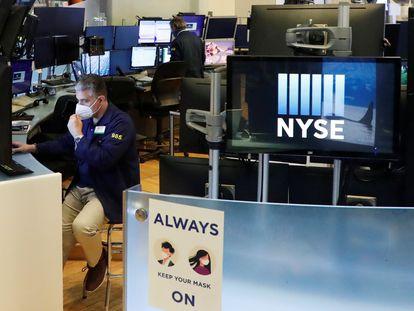 Un trabajador se ajusta la mascarilla en la Bolsa de Nueva York.