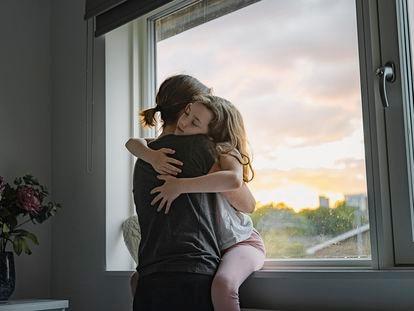 Una mujer y su hija se funden en un abrazo.
