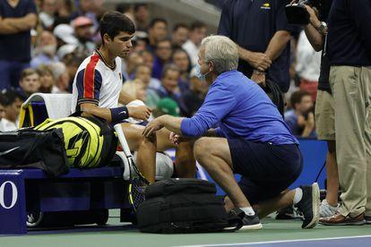 Carlos Alcaraz es atendido por el médico durante el partido contra Augger-Aliassime en la pista Arthur Ashe.