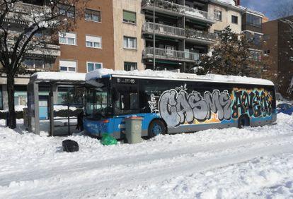 Un autobús de la EMT atrapado en la nieve durante el Temporal Filomena aparece con pintadas en una calle de Madrid.
