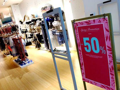 Un cartel anuncia rebajas en una tienda de ropa.