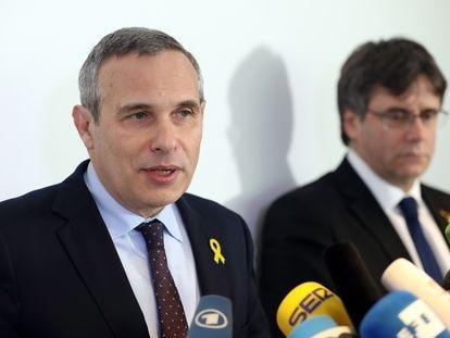 Josep Lluís Alay, jefe de la oficina de Carles Puigdemont, junto al expresidente catalán, en un acto en Berlín.