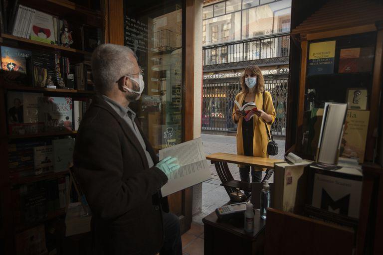 Javier Rodríguez, dueño de la Librería de Javier, de Alcalá de Henares, atiende a la autora del reportaje a la entrada de su tienda.
