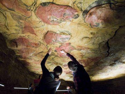Unos turistas observan las pinturas rupestres en la réplica de las Cuevas de Altamira, situada en la localidad cántabra de Santillana del Mar.