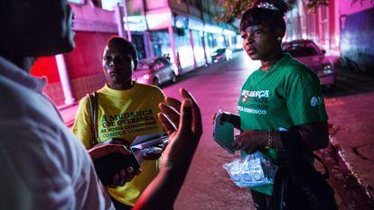 Armados con listas de mujeres para contactar, dos trabajadoras comunitarias hablan con personas en el distrito de luz roja del puerto de Maputo, Mozambique, para brindar información sobre prevención y derivación del VIH a quienes la necesitan.