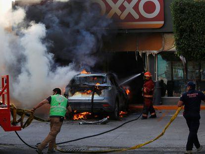 Bomberos apagan el fuego de un coche en Celaya, Guanajuato.