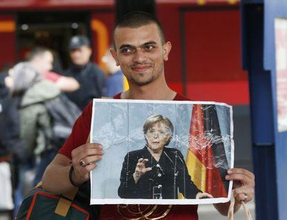 Un refugiados muestra una foto de Merkel al llegar a Múnich.