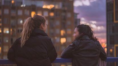 Dos adolescentes charlan en la terraza. A veces, a los padres les cuesta comunicarse con ellos.