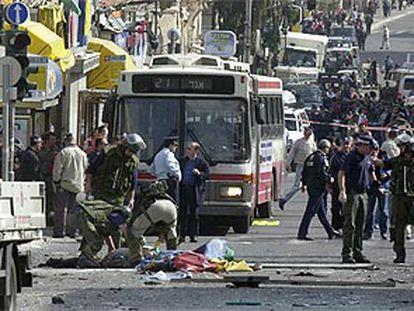 La policía israelí examina el cadáver del terrorista, tendido en el suelo con una sábana.